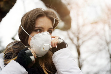 Woman outdoors in city with a face mask against infection and viruses such as flu, corona virus, sars or swine influenca