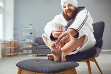 Photo sur cadre textile Pedicure Funny pedicure concept. Funny fat man in a bathrobe and a towel paints his nails