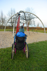 Kid in a wheelchair waiting on the playground and watching other kids climbing