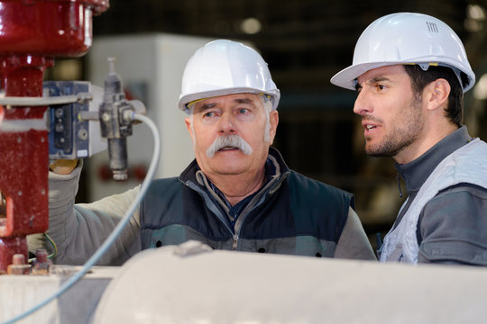 senior engineer and colleague looking at machine