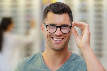 handsome man choosing glasses in optics store Fototapete