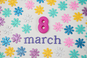 March made from purple letters, a purple 8 made of plastic and colorful little flowers on white background. International Women's Day decoration