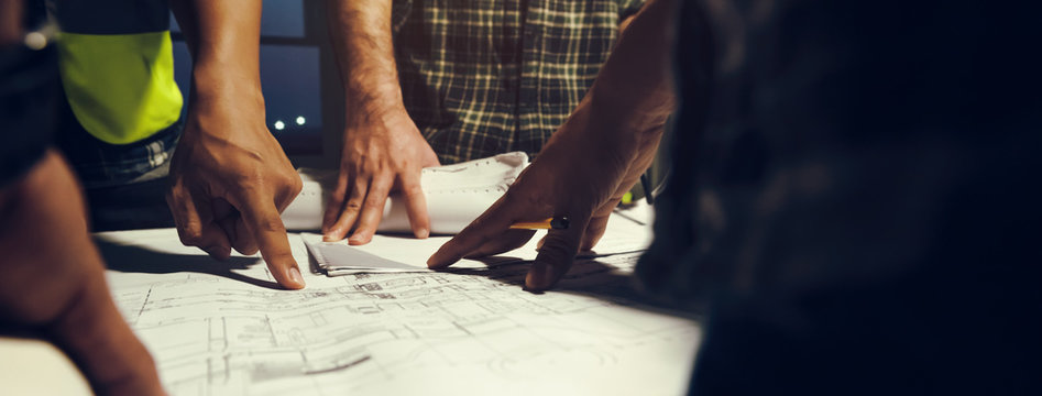 Construction engineers discussion with team members at meeting room with construction drawing on Desk, Pointed directly to the startup. Construction Business Banner background.