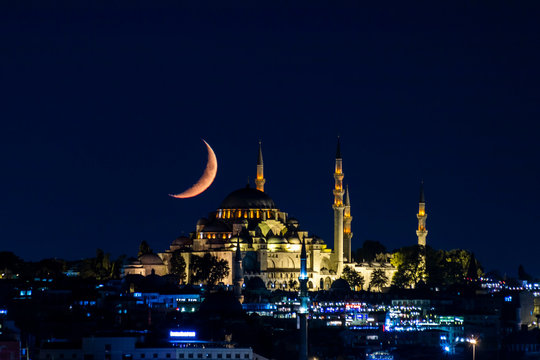 The moon stands like a crescent moon over the Fatih Mosque at night