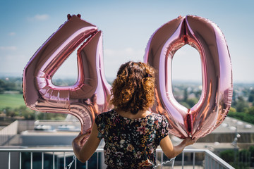 Attractive curly brunette celebrating her 40th birthday with big balloons