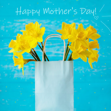 Happy mother's day greeting card. Spring yellow daffodils in a gift bag on a turquoise background