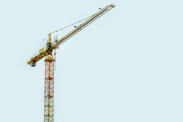 Building crane on sky background. Silhouette of industrial lifting equipment in construction site