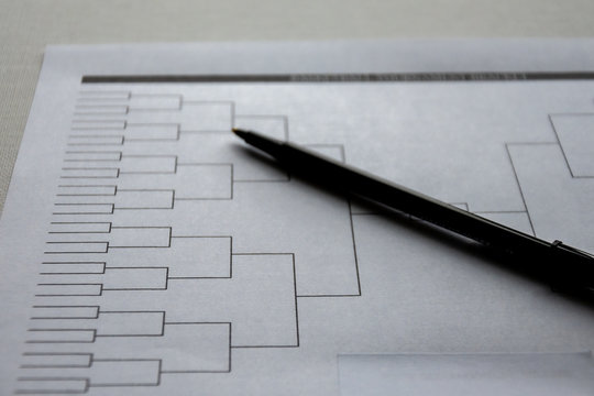 Blank basketball bracket grid on white paper with pen laying on top