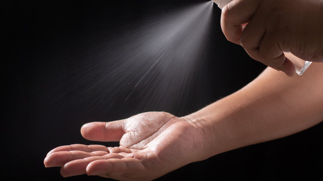 Male hands washing with alcohol spray to eliminate bacteria and viruses