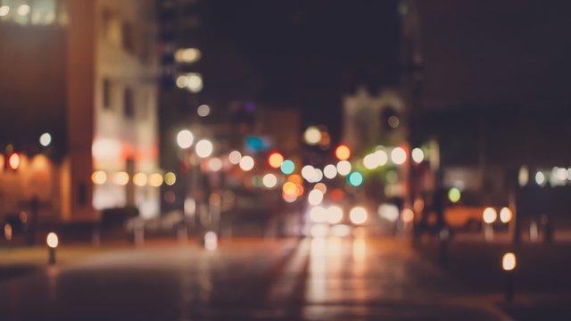 Abstract blur urban city street road with people walking and lighting bokeh for background.