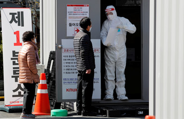 A medical worker in a protective gear offers consultation to people at the first stage screening post for checking coronavirus disease at Kyungpook National University Hospital in Daegu