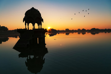 Fototapete - Gadsar Lake at Jaisalmer Rajasthan at sunrise with ancient architecture in silhouette