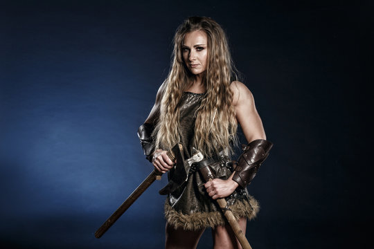 Beautiful female viking woman warrior in battle with big two-handed sword. Ancient times. Amazon fantasy blonde hair sexy girl.