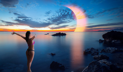 Long exposure image of Dramatic sky and seascape with rock Solar eclipse over the sea - Happy slim girl in red and black bikini  with raised up arms on the seashore in Alanya, Turkey Wall mural