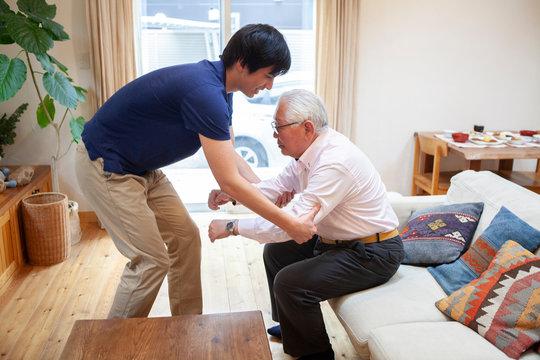 立ち上がりの介助をする男性介護士