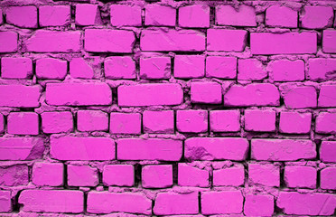Old pink brick wall. Brickwork from an old pink brick in a rustic style. The structure and pattern of the destroyed stone wall. Copy space