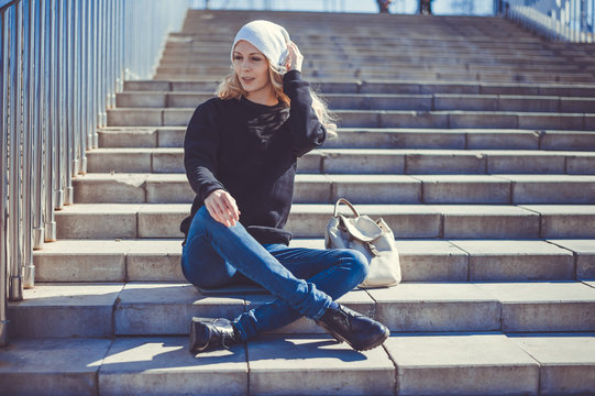 Fashion photo of a young beautiful woman in jeans, a black sweatshirt, a white knitted hat with a backpack
