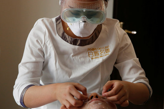 Beautician wearing protective mask and goggles attends to a customer with facial mask during treatment at the Pearl Deluxe beauty spa as the country is hit by an outbreak of the novel coronavirus, in Beijing