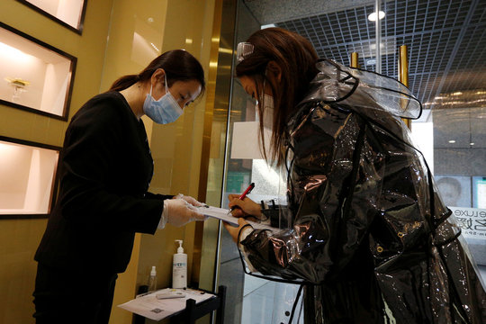 A customer wearing a raincoat, a face mask and goggles registers as she arrives at the Pearl Deluxe beauty spa for facial treatment, as the country is hit by an outbreak of the novel coronavirus, in Beijing