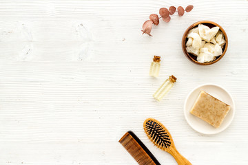 Cosmetics for hair care with argan and jojoba oil on white background top-down frame copy space
