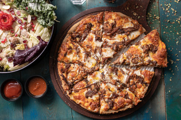 Roast beef pizza with colorful green salad