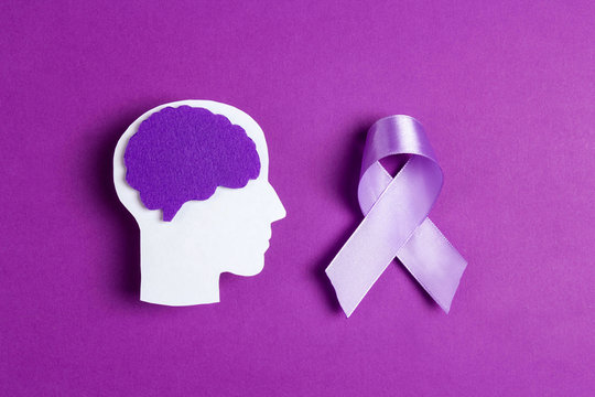 Purple awareness ribbon and brain symbol on a violet background.