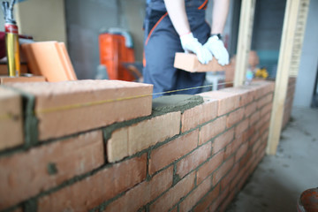 Skilled builder with bricks laying red blocks on well made masonry. Smart man in uniform using special tools and equipment. Building concept. Blurred background