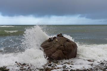 Wellen brechen sich an einem großen Stein am Strand