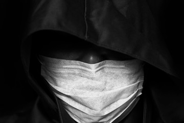 Man in hood and face mask on dark background. Black and white. Papier Peint