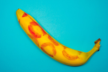 Red lipstick on a yellow banana on a blue background. Oral sex concept.