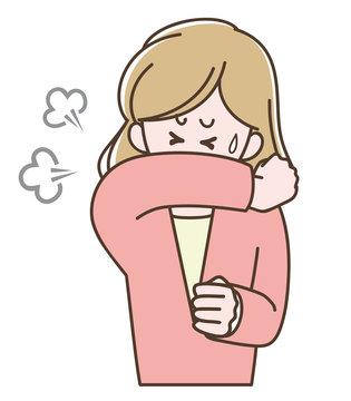 袖で口を覆って咳をする女性