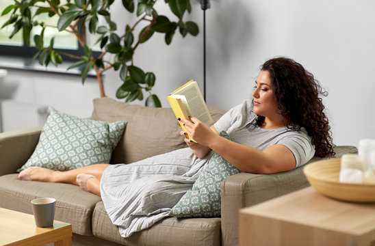 people and leisure concept - young woman reading book on sofa at home