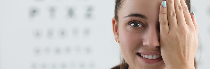Portrait of lady oculist smiling and looking at camera with happiness. Cheerful doctor standing in clinic office and covering left eye with tender hand. Vision test concept
