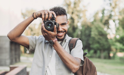Young man photographer takes photographs with dslr camera in a city. Travel, vacations, professional freelance work and active lifestyle concept Fotobehang