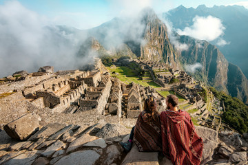 Couple dressed in ponchos watching the ruins of Machu Picchu