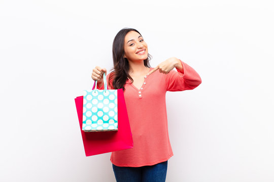 young latin pretty woman  against flat wall with shopping bags