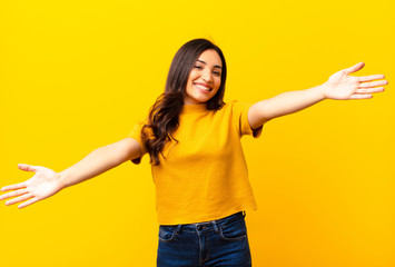 young latin pretty woman smiling cheerfully giving a warm, friendly, loving welcome hug, feeling happy and adorable against flat wall