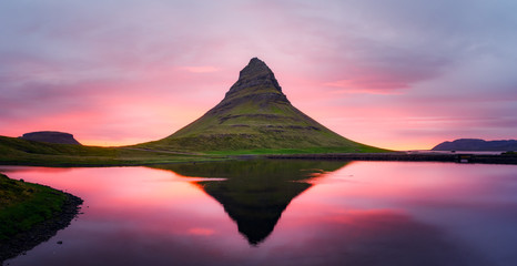 Foto op Canvas Lichtroze Picturesque panoramical landscape with Kirkjufell mountain, clear lake and cloudscape in sunset sky