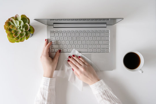 A woman worker cleaning with antivirus wet wipe a laptop and a working office desk before starting work for protect herself from bacteria and virus.
