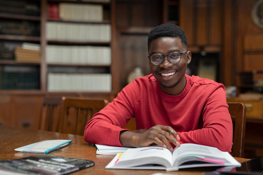 Happy university student in library