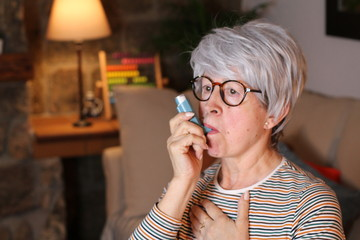 Senior woman using asthma inhaler at home