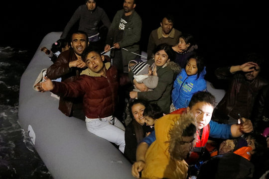 Migrants wave and shout for help, following a failed attempt to cross to the Greek island of Lesbos, as a Turkish Coast Guard boat aproaches them on the waters of the North Aegean Sea, off the shores of Canakkale