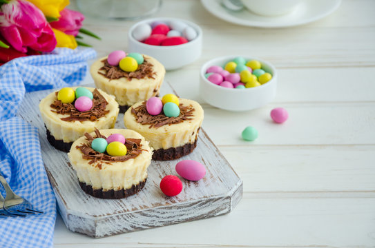 Easter mini brownie cheesecake Bird's Nest with chocolate and candy eggs. Easter dessert. Funny food idea for children. Horizontal orientation. Selective focus. Copy space