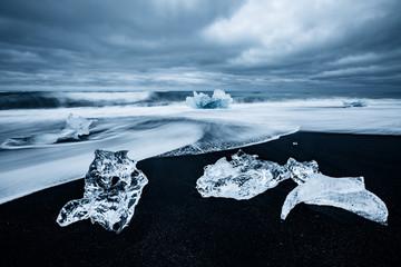 Wall Mural - Incredible pieces of the iceberg sparkle on black sand. Location Jokulsarlon lagoon, Diamond beach, Iceland, Europe.