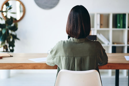 Young woman sitting at wooden desk and working in office