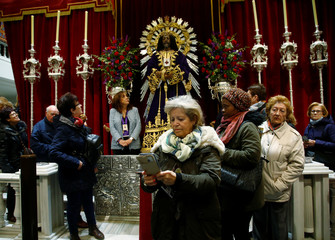 A worshiper stands next to the icon of Jesus de Medinaceli after religious authorities asked to abstain from kissing its feet amidst coronavirus fears at the Basilica of Jesus de Medinaceli in central Madrid
