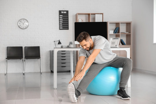Man doing exercises with fitness ball in office