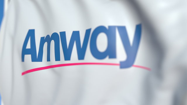 Flying flag with Amway logo, close-up. Editorial 3D rendering