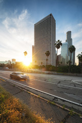 Wall Mural - Los Angeles downtown with highway and moving car. Sunrise in LA financial district