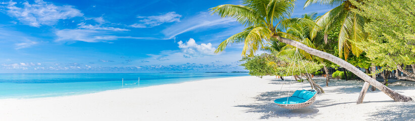 Tropical beach panorama as summer landscape with beach swing or hammock and white sand and calm sea...